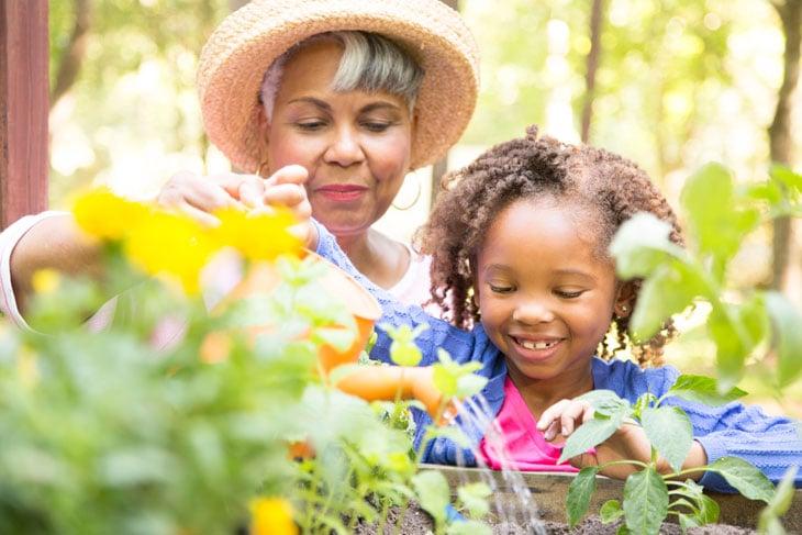 Grandmother-teaching-granddaughter-gardening