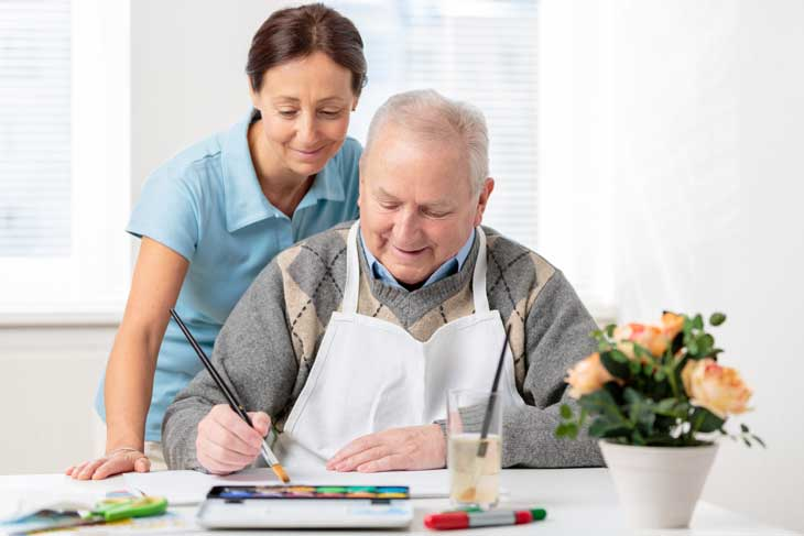 senior-man-painting-with-occupational-therapist