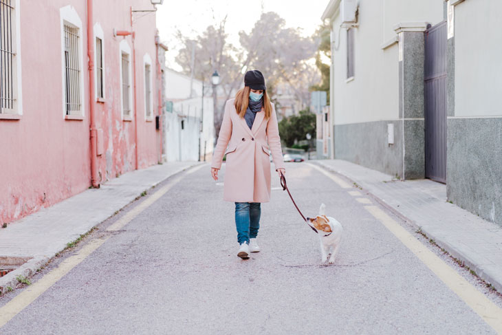 women-walking-her-dog-while-practicing-social-distancing