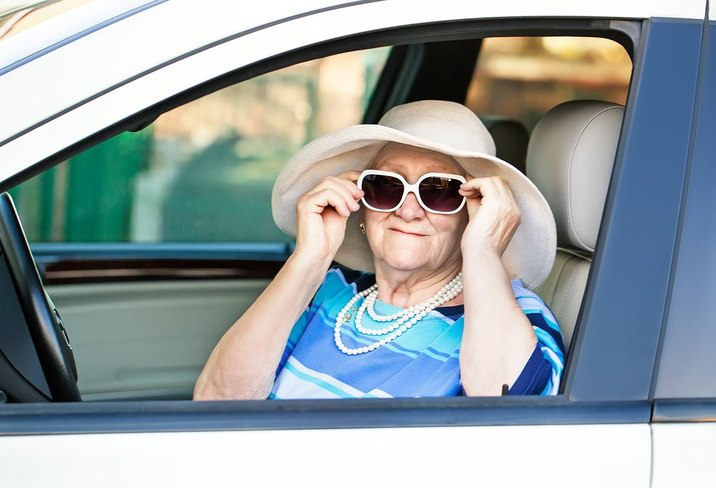 senior wearing sunglasses in car