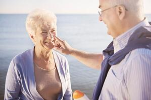 senior man putting sunscreen on senior woman