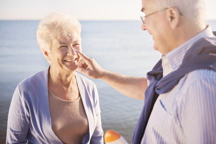 senior man putting sunscreen on senior woman