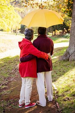 seniors standing under sun umbrella
