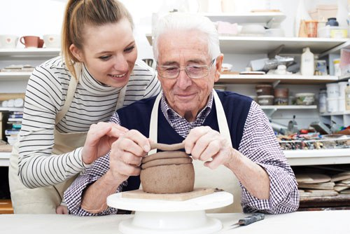 Senior doing pottery with woman