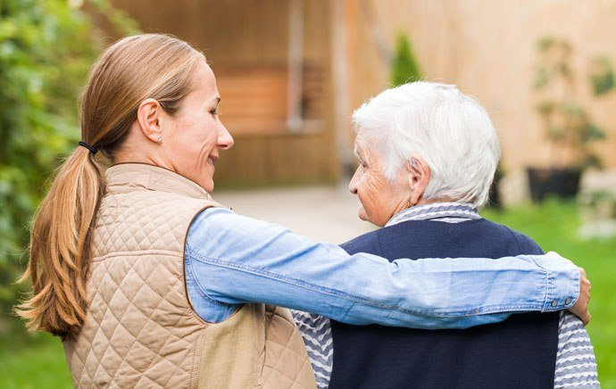 caregiver with arm around senior