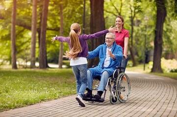 child running to man in wheelchair
