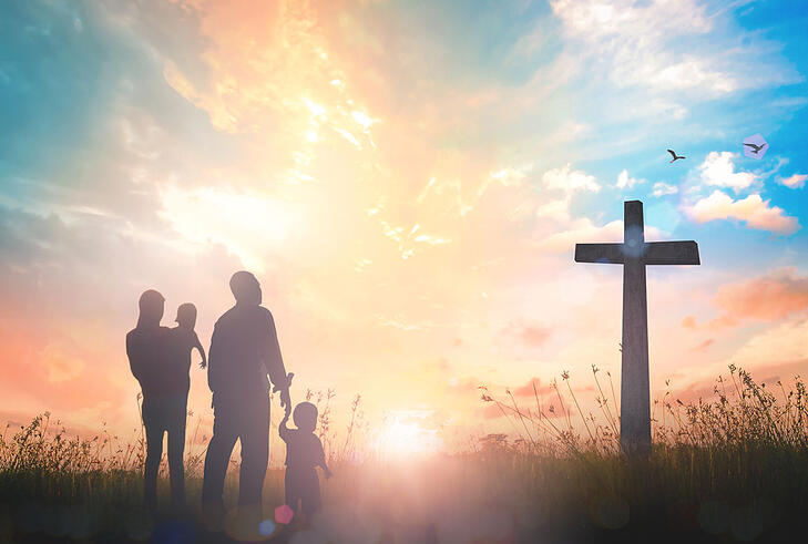 family and cross silhouette in front of sunset